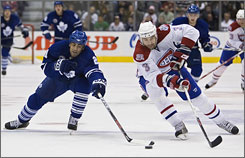 Toronto Maple Leafs forward Jamal Mayers, left, and Montreal Canadiens defenseman Ryan O'Byrne battle for the puck during the second period of their game in Toronto. Five players scored for the Maple Leafs in their 6-3 win.