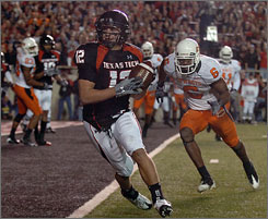 Texas Tech's Eric Morris scores a touchdown ahead of Oklahoma State's Ricky Price during their college football game in Lubbock, Texas. The third-ranked Red Raiders improved to 10-0 with the win over the Cowboys.