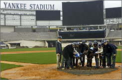 Residents of the Bronx along with former Yankee players dump dirt obtained from home plate of the old stadium onto the surface of the new stadium on Saturday.