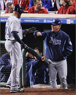 Manager Joe Maddon, congratulating outfielder Carl Crawford in Game 3 of the World Series, has helped turn around a Tampa Bay Rays franchise that had never posted a winning record or made the playoffs in its history until this season.