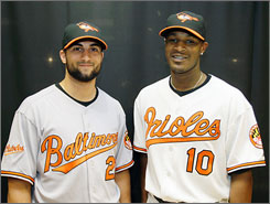 Outfielders Nick Markakis, left, and Adan Jones model the new away and home uniforms for the 2009 Baltimore Orioles at Wednesday's unveiling.