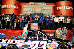 Johnny Benson, center, celebrates winning the 2008 NASCAR Craftsman Truck Series Championship after finishing seventh in the Ford 200 at Homestead-Miami Speedway in Homestead, Fla.