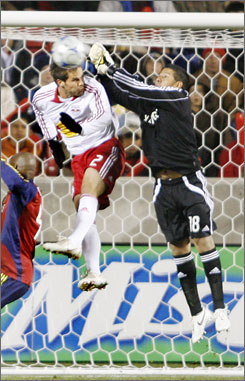 Real Salt Lake goalkeeper Nick Rimando, right, punches the ball away before it gets to New York Red Bulls defender Kevin Goldthwaite during the first half of their Major League Soccer Western Conference Final game in Sandy, Utah.
