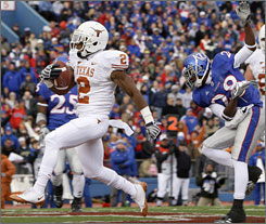 Texas running back Vondrell McGee beats Kansas cornerback Daymond Patterson into the end zone for the game's first touchdown.