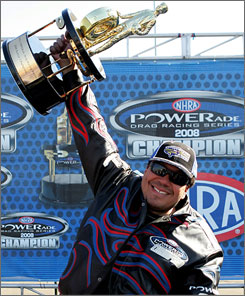 Cruz Pedregon hoists the trophy as Funny Car champ for the second time in his NHRA career.