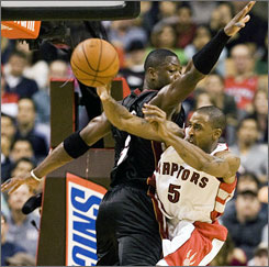 Raptors guard Will Solomon absorbs a mid-air collision with Heat star Dwyane Wade late in the fourth quarter.