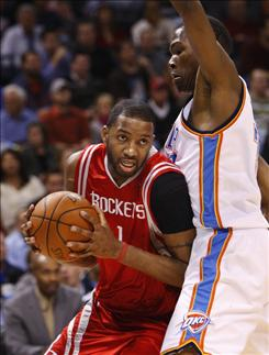 Houston Rockets guard Tracy McGrady, left, had to leave Monday's game in the second half after aggravating his left knee, which was operated on this offseason. He planned to have an MRI on Tuesday.