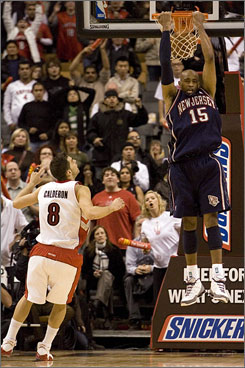 The New Jersey Nets' Vince Carter hangs from the hoop after scoring the game-winning basket in overtime against the Raptors in Toronto. Carter scored the game-winner on a reverse dunk off an inbounds pass from Bobby Simmons with 2.9 seconds left.