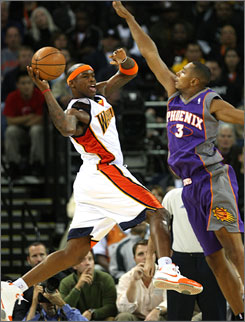 Al Harrington looks to pass as he's defended by Boris Diaw of the Phoenix Suns in a game last season. Harrington's playing time with the Golden State Warriors has decreased this season, and the team struck a deal to send him to the New York Knicks.