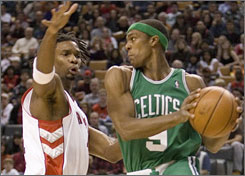 Celtics guard Rajon Rondo, right, feels pressure from Raptors defender Chris Bosh during the first quarter.