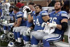 Lions players watch as the final minutes of their 11th consecutive loss to start the season tick off the clock.