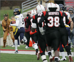 West Virginia's Pat White ran and passed for a total of 322 yards and had a hand in five touchdowns against Louisville.