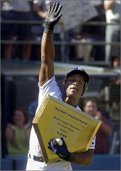 Rickey Henderson of the San Diego Padres holds a commemorative gold home plate after he broke Ty Cobb's career record for runs scored with his 2,246th. Henderson also holds the record for career stolen bases.