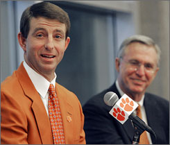 Clemson athletics director Terry Don Phillips, right, looks on as new football coach Dabo Swinney speaks at a news conference. Swinney guided the Tigers to four wins in their last five games for a 7-5 record and a bowl appearance.