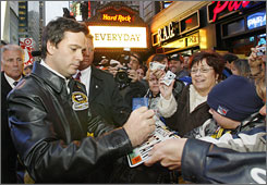 NASCAR champ Jimmie Johnson signs autographs for fans in New York's Times Square.