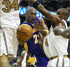 The Lakers' Kobe Bryant tries to pass around the Wizards' Antawn Jamison during the third quarter. Bryant scored 23 points, grabbed seven rebounds and dished 7 assists as Los Angeles barely beat the worst team in the Eastern Conference.
