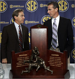 Alabama coach Nick Saban, left, and Florida coach Urban Meyer take sides behind the SEC Championship trophy during a Friday news conference.