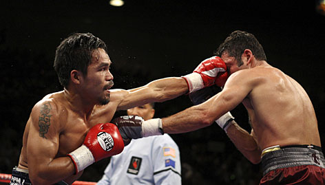 Manny Pacquiao, left, lands a left on Oscar De La Hoya during their fight in Las Vegas. Pacquiao won when De La Hoya refused to come out of his corner before the ninth round.