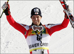 Benjamin Raich raises his skis in triumph after posting a narrow win in the World Cup giant slalom at Birds of Prey.