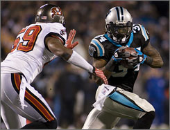 The Panthers' DeAngelo Williams, running around the Buccaneers' Cato June, rushed for a career-high 186 yards and two touchdowns to help Carolina take a one-game lead in the NFC South.