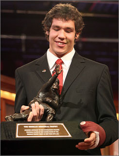 Oklahoma quarterback Sam Bradford takes hold of the Heisman Trophy after beating out Texas QB Colt McCoy and Florida QB Tim Tebow for the award.