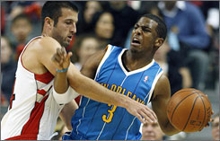 Hornets guard Chris Paul shields the ball from Raptors defender Jason Kapono during the first half.