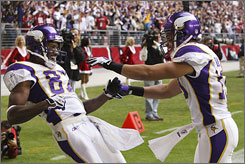 Bobby Wade, right, celebrate a touchdown by Vikings receiver Bernard Berrian, left, in the first quarter.