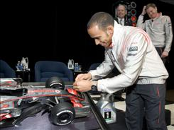 Lewis Hamilton, the 2008 Formula One champion, adds the No. 1 to a model of his Formula One race car during a visit Tuesday to the Fairfax, Va., office of sponsor ExxonMobil.