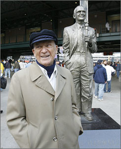Detroit Tigers radio voice Ernie Harwell stops in front of his statue outside Comerica Park just before the 2006 World Series. Harwell got his first major league announcing job 60 years ago when the Brooklyn Dodgers sent a player to the Atlanta Crackers of the Southern Association.