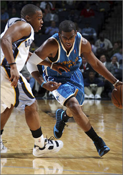 New Orleans Hornets guard Chris Paul, right, tries to dribble past Memphis Grizzlies guard Kyle Lowry during the fourth quarter of their game in Memphis. The Hornets defeated the Grizzlies 91-84.