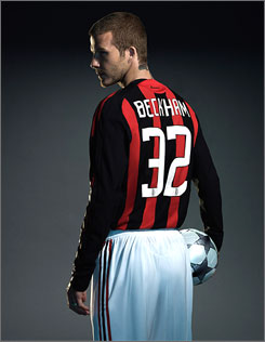 David Beckham poses in his new No. 32 AC Milan jersey after arriving in Italy on Saturday.