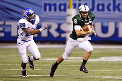 South Florida quarterback Matt Grothe, running away from a Memphis defender, became the Big East's career total offense leader by throwing for 236 yards and three touchdowns in the Bulls' St. Petersburg Bowl victory.