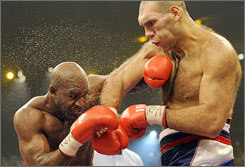 Nikolai Valuev catches Evander Holyfield with a right hand during their heavyweight title bout in Switzerland. Valuev retained his WBA belt with a majority decision.