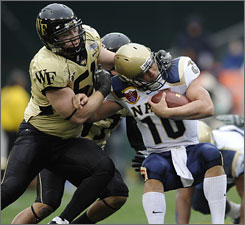 Wake Forest's John Russell drags down Navy's Kaipo-Noa Kaheaku-Enhada during the first half of the Demon Deacons' victory in the EagleBank Bowl in Washington.