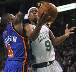 Celtics point guard Rajon Rondo goes to the basket against Knicks counterpart Nate Robinson during the second half. Rondo scored 18 of his 26 points in the third quarter as Boston tied a franchise record with its 18th consecutive win.