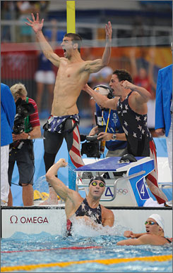The USA's Michael Phelps and Garrett Weber-Gale rejoice after Jason Lezak's (in water) anchor leg won the 4x100-meter freestyle relay.