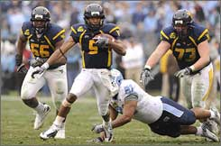 West Virginia's Pat White runs through the North Carolina defense Saturday.