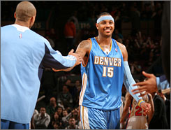 Carmelo Anthony gets a warm welcome from the Nuggets bench after scoring a game-high 32 points in his return from a three-game absence.
