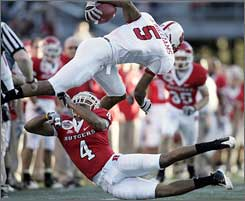 Rutgers defensive back David Rowe upends N.C. State wide receiver Jarvis Williams.