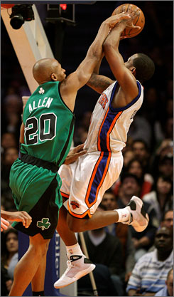 New York Knicks guard Chris Duhon goes up for a shot as Boston Celtics guard Ray Allen defends during the fourth quarter of the Knicks' 100-88 victory at Madison Square Garden in New York.