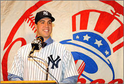 Mark Teixeira is all smiles as he puts on the Yankee pinstripes for the first time Tuesday when the Yankees officially announced the signing of his 8-year, $180 million contract.