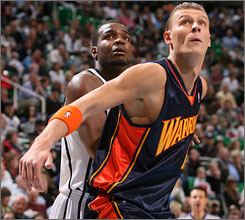 Golden State center Andris Biedrins boxes out Utah's Paul Millsap on the way to another double-double night (14 points, 17 rebounds) on Jan. 5.