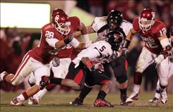 "Oklahoma defenders, including linebacker Austin Box (No. 12), surround Texas Tech wide receiver Michael Crabtree (No. 5) in November. Box says critics of the Sooners' defense are ""fueling us."""