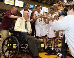 Northern State basketball coach Don Meyer celebrates his 903rd career coaching win with his team.