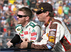 Dale Earnhardt Jr., left, chats with fellow driver David Reutimann before a NASCAR Sprint Cup race Nov. 9 in Avondale, Ariz. Earnhardt Jr. says he is opposed to a schedule reduction for the Series even during these tough economic times.