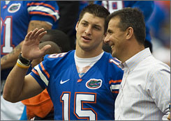 Tim Tebow and Florida coach Urban Meyer take in the Sunday celebration at Florida's stadium.