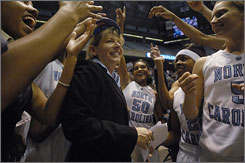 North Carolina coach Sylvia Hatchell is surrounded by her team after notching the 800th victory of her career.
