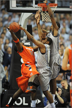 Georgetown's Austin Freeman, center, and Greg Monroe double-team Syracuse's Paul Harris on a shot during the first half of the 12th-ranked Hoyas' 14-point victory in Washington.