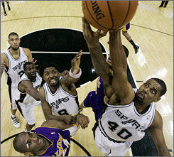 Lakers guard Kobe Bryant, bottom left, looks on as teammate Trevor Ariza, second from right, competes with Spurs center Kurt Thomas (40) and guard Roger Mason (8) for a rebound during the second quarter of San Antonio's 112-111 win at home.