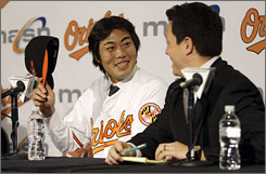 New Orioles pitcher Koji Uehara smiles at his interpreter Kenta Yagi after his introduction at Camden Yards.